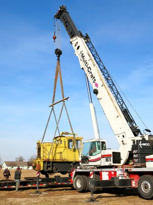 Photo by Randy Moll A 1943, 25-ton, switch locomotive is lifted by crane from a truck trailer at the Tired Iron of the Ozarks showgrounds on Thursday. The club plans to restore the old engine to its original condition as a showpiece.