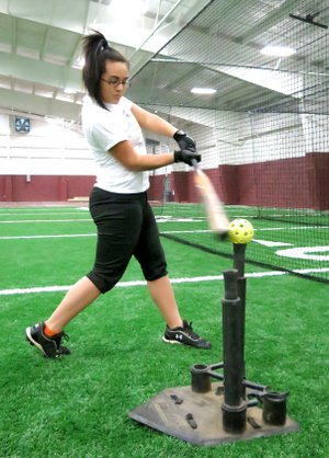 Photo by Randy Moll Courtney Brown practices her swing during softball practice inside the new multi-purpose athletic facility on the Gentry High School campus on Jan. 29.
