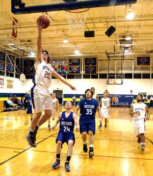 Photo by Mike Eckels Terry Kell (Decatur #20) flies through the air for a lay up during the Jan. 30 game with the Westside Rebels at Peterson Gym. Kell was the second leading scorer, with 13 points. The Bulldogs won the game, 66 to 44, and improve their record to 8 and 8 overall.
