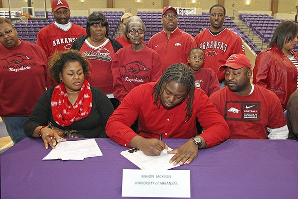 El Dorado High School defensive lineman Bijhon Jackson signs his letter-of-intent to play football for the University of Arkansas on National Signing Day at the EHS Wildcat Arena Wednesday. Jackson was surrounded by his mother Michelle, seated left, and father Anthony, seated right, many family members, classmates, teammates and coaches.