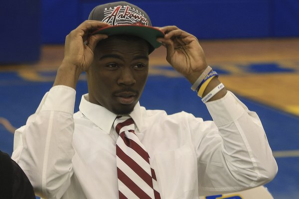North Little Rock's Juan Day puts on a Razorback hat Wednesday morning after signing to play football for the University of Arkansas.