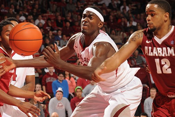 Arkansas freshman Bobby Portis, center, collects a rebound in front of Alabama senior Trevor Releford (12) during the second half of play Wednesday, Feb. 5, 2014, in Bud Walton Arena in Fayetteville.