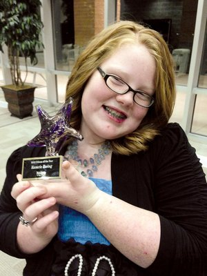 Kamrie Ewing of Dover holds the award she received as Russellville Citizen of the Year. The fifth-grader began raising money for charity about 18 months ago and started a nonprofit organization, Kamrie's Colorful Creations. She also received the Outstanding Community Service Award from the Dover Area Chamber of Commerce.