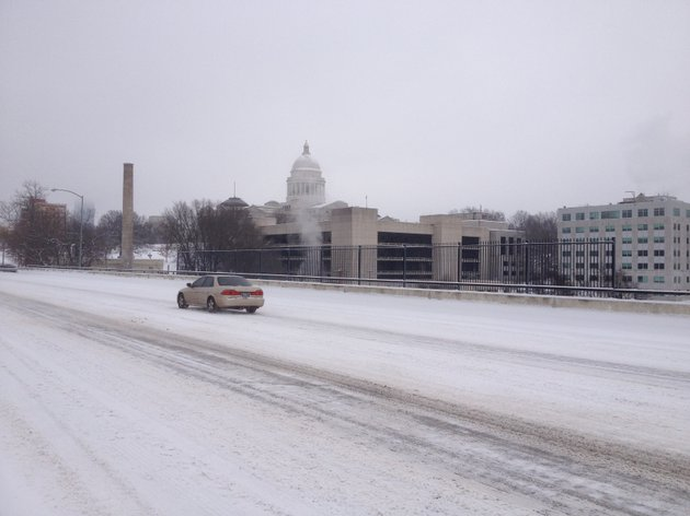 a-car-moves-along-a-snow-covered-markham-street-near-the-arkansas-state-capitol-saturday-morning