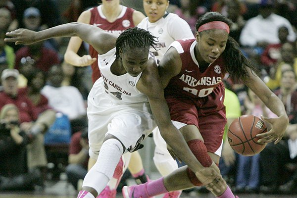 South Carolina's Aleighsa Welch (24) battles for a loose ball with Arkansas' Jessica Jackson (00) during an NCAA college basketball game Sunday, Feb. 9, 2014, in Columbia, S.C. (AP Photo/Mary Ann Chastain)