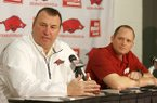 Arkansas football defensive coordinator and secondary coach Robb Smith (right) listens at a press conference Monday morning Feb. 10, 2014 at the Fred W. Smith Football Center. Head football coach Bret Bielema (left) answers a question.