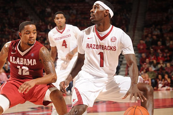 Arkansas senior Mardracus Wade (1) looks to drive as Alabama senior Trevor Releford defends during the second half of play Wednesday, Feb. 5, 2014, in Bud Walton Arena in Fayetteville.