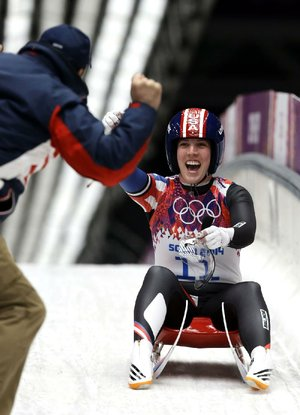 American Erin Hamlin is greeted by her coach after finishing her final run to win the bronze medal in women's luge.