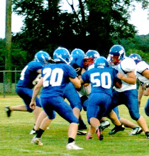 Photo by Mike Eckels Matt Lee (#50) loves to be in the thick of things as he and fellow Bulldogs effectively shut down a run during the Decatur/Mountainburg game of Sept. 20. Lee also participates on the senior basketball team. Although he makes an outstanding player in any sport, his first love is football.
