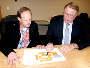 Photo by Dodie Evans Richard Page, Gravette superintendent of schools (right), and facilities committee member Bryan Johnson look over a revised floor drawing of an elementary school being considered at Bella Vista. It was presented at a meeting of the committee Monday afternoon. Architects have reduced the building from 68,000 square feet to the board s requested 61,000 square-foot structure.