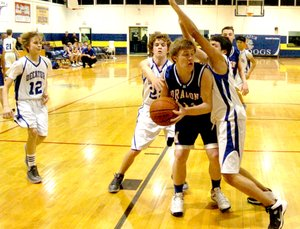 Photo by Mike Eckels Decatur s Ryan Shaffer (#22) and Jaffett Puga (#30 turn sideways on right) block a Mountainburg player from shooting the ball while Bracey Owens (#12) sets up to cut off the players escape. The Bulldog junior high boys lost to the Dragons 24 to 20 Feb. 6 at Peterson Gym in Decatur.