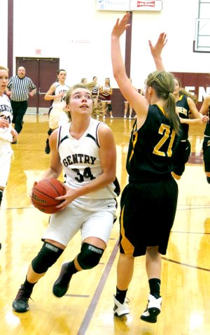 Photo by Randy Moll Haley Borgeteien-James, Gentry sophomore, drives past Taylor Hartin of Prairie Grove to take a quick shot under the basket during play on Friday in Gentry.
