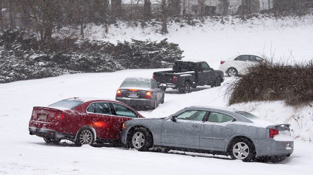 cars-that-lost-traction-sit-on-the-eastbound-ramp-from-joseph-bryan-boulevard-to-holden-road-during-a-snowfall-in-greensboro-nc-wednesday-feb-12-2014-a-major-winter-slammed-into-north-carolina-wednesday-turning-homebound-commutes-that-typically-take-minutes-into-hours-long-ordeals-as-traffic-slowed-to-a-slippery-slog-and-threatening-to-leave-many-areas-dark-because-of-power-outages