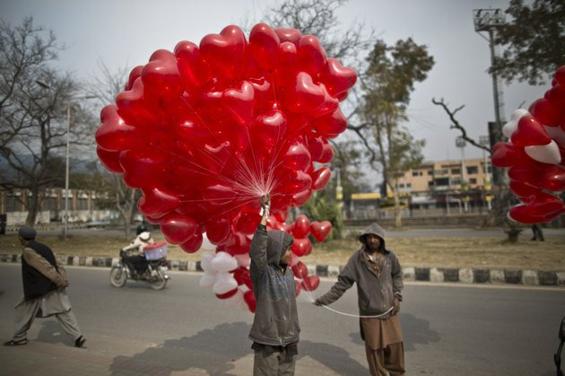 a-pakistani-boy-stands-on-a-roadside-along-with-other-vendors-holding-red-heart-shaped-balloons-hoping-to-sell-them-on-valentines-day-in-islamabad-pakistan-on-friday-feb-14-2014