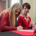 Payton Stumbaugh, Springdale Har-Ber senior track athlete, signs a national letter Friday, Feb. 14, ...