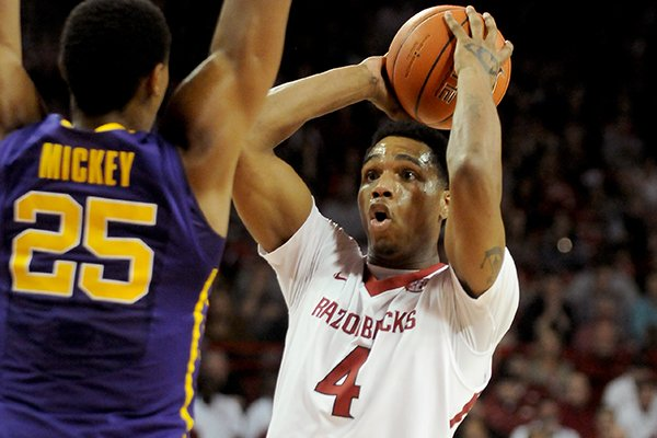 Arkansas's Coty Clarke looks to pass under pressure from LSU's Jordan Mickey during the game between Arkansas and LSU on Saturday February 15, 2014 in Bud Walton Arena in Fayetteville.