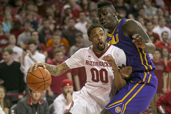 Arkansas guard Rashad Madden (00) drives to the basket against LSU forward Johnny O'Bryant III (2) during the second half of an NCAA college basketball game on Saturday, Feb. 15, 2014, in Fayetteville, Ark. (AP Photo/Gareth Patterson)