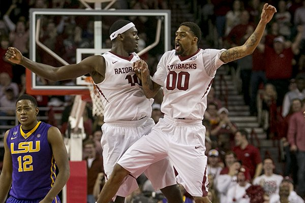 Arkansas forward Bobby Portis (10) and guard Rashad Madden (00) celebrate at center court after completing an alley-oop dunk during the second half of an NCAA college basketball game on Saturday, Feb. 15, 2014, in Fayetteville, Ark. Madden led all scorers with 21 points in Arkansas' 81-70 win. (AP Photo/Gareth Patterson)