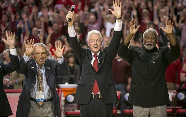"""Eddie Sutton, left, former President Bill Clinton, center, and Nolan Richardson, right, call the """"Hogs"""" during halftime of an NCAA college basketball game between Arkansas and LSU on Saturday, Feb. 15, 2014, in Fayetteville, Ark. (AP Photo/Gareth Patterson)"""