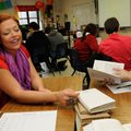 Teacher Yvonne Scorse works with students on Friday Feb. 14 2014 during the hidden-cover book exerci...