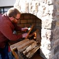 Travis Bounds with Builders Stone & Supply builds a fire in an outdoor fireplace outside the Northwe...