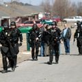 Springdale Police walk back down Twin County Street on Friday, Feb. 14, 2014, following a standoff a...