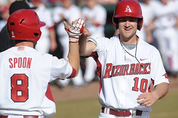 Arkansas left fielder Joe Serrano (10) is congratulated at the plate by right fielder Tyler Spoon as he scores a run after hitting an RBI double to break a 3-3 tie during the seventh inning Sunday, Feb. 16, 2014, against Appalachian State at Baum Stadium in Fayetteville.