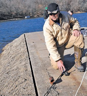 STAFF PHOTO FLIP PUTTHOFF  Jeff Overturf checks his fishing rod Friday hoping to catch some trout at Lake Atalanta in Rogers. The Arkansas Game & Fish Commission stocks the lake with trout each winter.