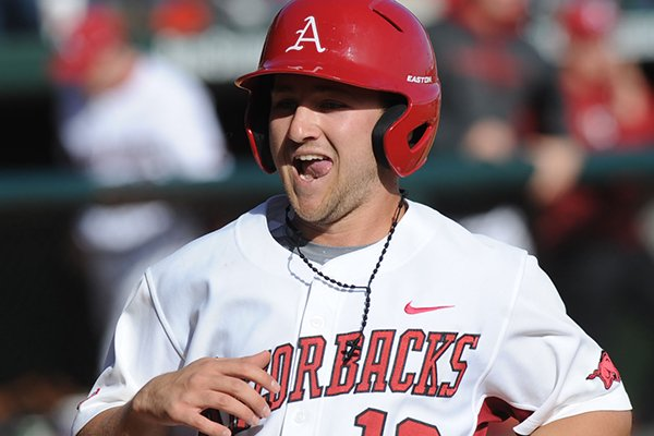 Arkansas left fielder Joe Serrano smiles as he scores a run after hitting an RBI double to break a 3-3 tie during the seventh inning Sunday, Feb. 16, 2014, against Appalachian State at Baum Stadium in Fayetteville.