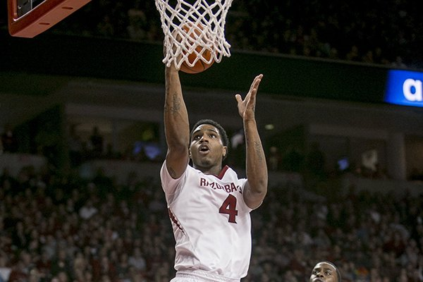 Arkansas guard Coty Clarke (4) drives past LSU guard Anthony Hickey (1) for a layup during the second half of an NCAA college basketball game Saturday, Feb. 15, 2014, in Fayetteville, Ark. (AP Photo/Gareth Patterson)