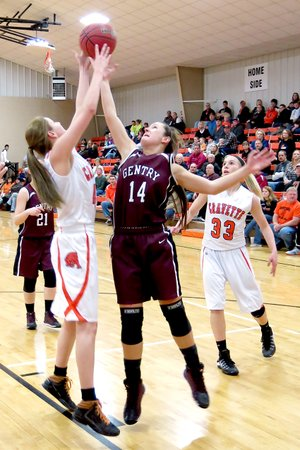 Photo by Randy Moll Gravette s Sydney Hicks and Gentry s Kristen Flesner vie for the rebound during play between the two teams on Feb. 11 at Gravette. Kylee Davis, of Gravette, looks on.