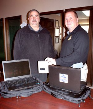 Photo by Dodie Evans Gravette Police Chief Bower, right, and Sgt. Rusterholz show new computers received by the Gravette Police Department. Bower is holding a box which held one of the cameras.