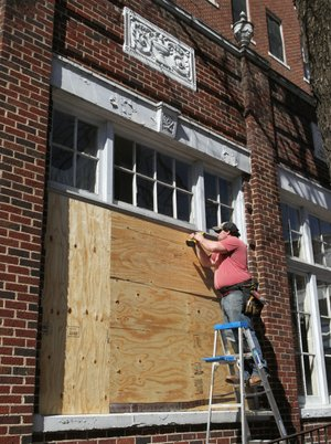 Jared Yarberry Construction employee Tyler Vines screws a piece of plywood over a window at the Majestic Hotel on Monday, February 17, 2014. The company was boarding up all the windows and doors on the building Monday.