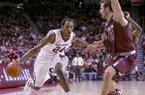 Arkansas guard Michael Qualls (24) fakes to the basket against South Carolina forward Mindaugas Kacinas (25) during the first half of an NCAA college basketball game, Wednesday, Feb. 19, 2014, in Fayetteville, Ark. (AP Photo/Gareth Patterson)