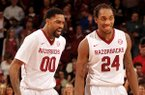 Arkansas players Rashad Madden and Michael Qualls head to the bench for a time out in the second half of Wednesday's game at Bud Walton Arena in Fayetteville.