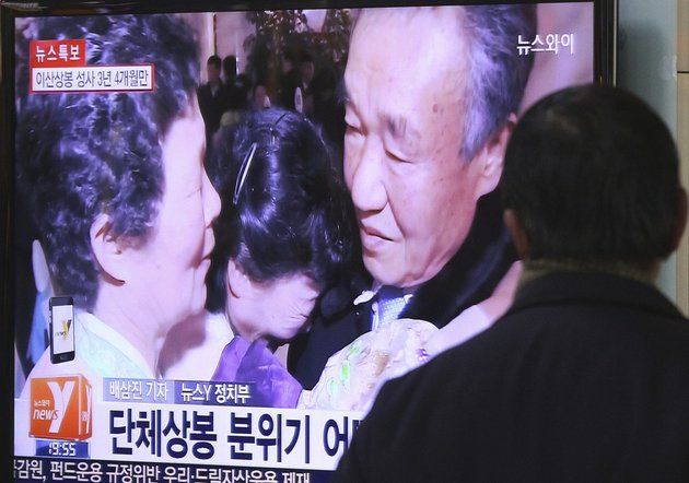 a-man-watches-a-tv-news-program-showing-south-and-north-korean-family-reunion-meeting-at-diamond-mountain-resort-in-north-korea-at-seoul-railway-station-in-seoul-south-korea-on-thursday-feb-202014-the-words-on-the-screen-reads-group-reunion-meeting