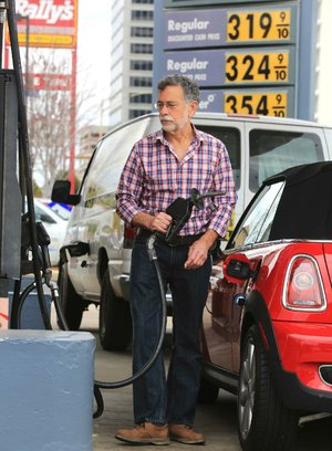 Arkansas Democrat-Gazette/RICK MCFARLAND --02/20/14--   Dom Yezzi cq, of North Little Rock, finishes gassing up his car at a Shell station, on Broadway at West 8th streets in Little Rock Thursday.