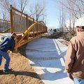 Joe Hatfield (left), with Multi-Craft Contractors, Inc., helps guide a 90 foot long pedestrian bridg...