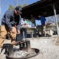 Alejandro Alvarado cooks thin-sliced steak over a campfire for his Rogers High School classmates on ...