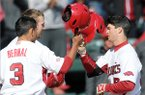 Arkansas' Michael Bernal, from left clockwise, and Bobby Wernes congratulate Andrew Benintendi on his home run Sunday, Feb. 23, 2014, while crossing home plate during the game against Eastern Illinois at Baum Stadium in Fayetteville.