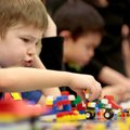 "Dominick Morgan, 5, of Prairie Grove ""drives"" his Lego-created vehicle through blocks on the table o..."