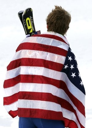 Men's giant slalom gold medalist Ted Ligety of the United States wears the American flag on the podium at the Sochi 2014 Winter Olympics, Wednesday, Feb. 19, 2014, in Krasnaya Polyana, Russia.(AP Photo/Charles Krupa)