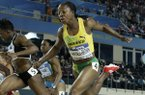 This is a Sunday, March 11, 2012 file photo of Jamaica's Veronica Campbell-Brown, right, as she crosses the finish line ahead of Ivory Coast's Murielle Ahoure, left, as Campbell Brown wins the gold medal in the Women's 60m race during the World Indoor Athletics Championships in Istanbul, Turkey. (AP Photo/Matt Dunham/ File)