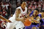LSU's Jarell Martin tries to steal the ball from Arkansas's Michael Qualls during the first half of the game between Arkansas and LSU on Saturday February 15, 2014 in Bud Walton Arena in Fayetteville.