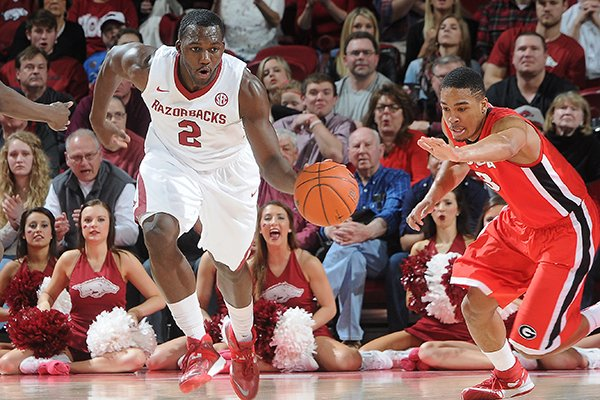 Arkansas' Alandise Harris, center, flies back down the court and through Brandon Morris, left, and Juwan Parker, both of Georgia, Saturday, March 1, 2014, during the second half of the game at Bud Walton Arena in Fayetteville