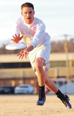 STAFF PHOTO ANDY SHUPE Austin Culp catches a disc during practice Thursday in Fayetteville.