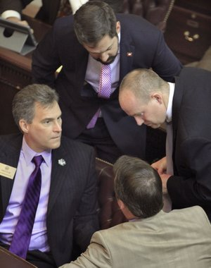 Arkansas Democrat-Gazette/BENJAMIN KRAIN State Rep. Charlie Collins, R-Fayetteville, left, House Minority Leader Greg Leding, D-Fayetteville, top, Jeff Wardlaw, D-Warren, right, and Rep John Burris, R-Harrison, discuss funding for the private option to expand Medicaid coverage during a recent House session in Little Rock.
