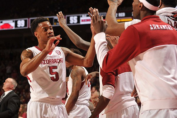 Arkansas guard Anthlon Bell gets high fives from his teammates as he leaves the game in the second half of Wednesday night's game against Ole Miss at Bud Walton Arena in Fayetteville.