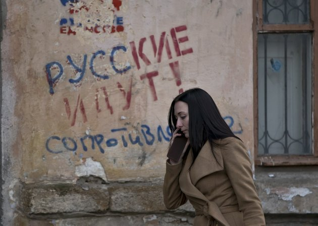 a-woman-passes-by-a-graffiti-that-reads-the-russians-are-coming-resistance-in-simferopol-ukraine-on-friday-march-7-2014-ukraine-lurched-toward-breakup-thursday-as-lawmakers-in-crimea-unanimously-declared-they-wanted-to-join-russia-and-would-put-the-decision-to-voters-in-10-days