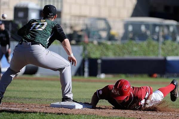 Arkansas shortstop Brett McAfee dives into first base on a pickoff throw during a game Friday, March 7, 2014 at Evans Diamond in Berkeley, Calif.